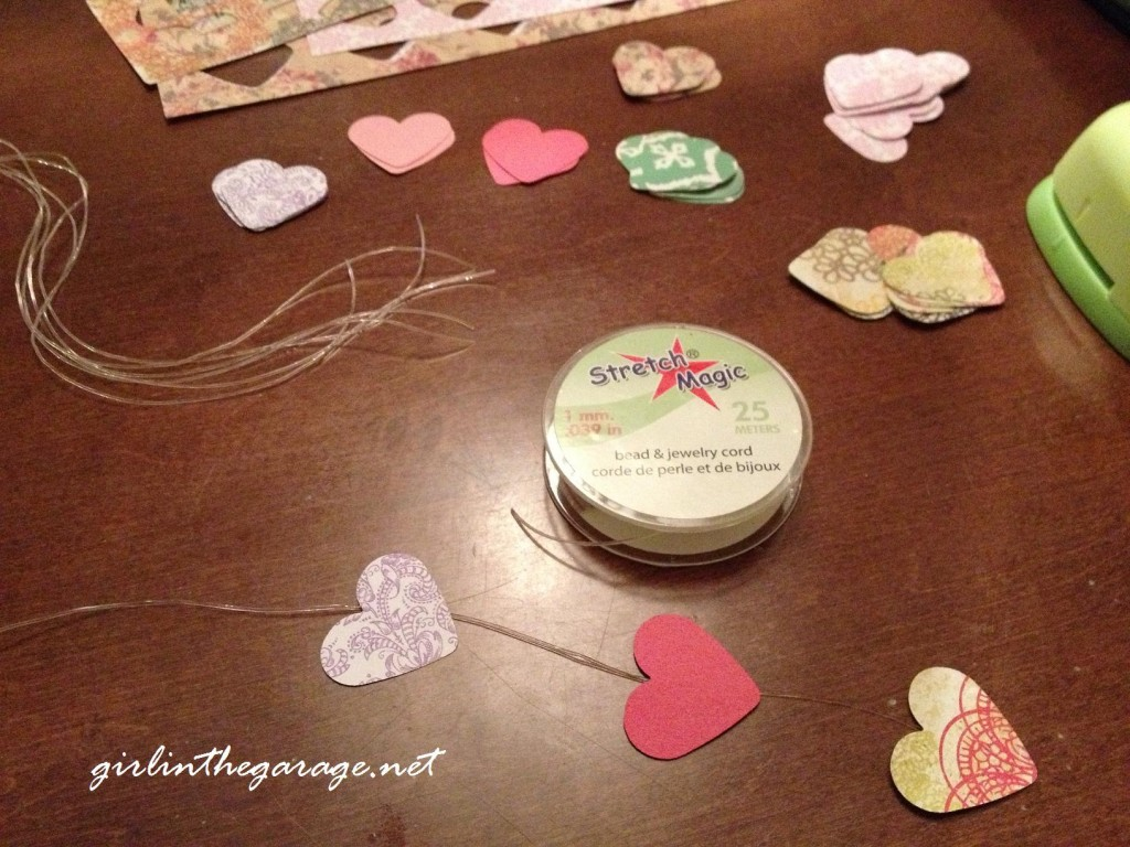Taping hearts to cord for Valentine's Day mobile