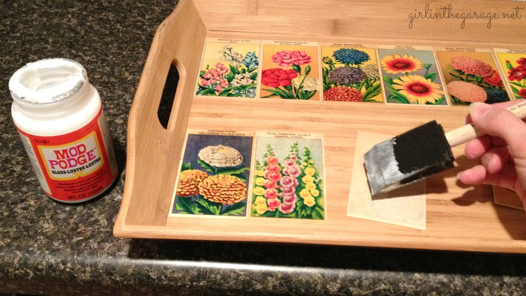 Using Mod Podge to glue flower labels to the tray. Girl in the Garage