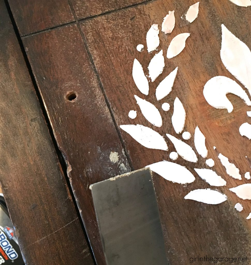 Add amazing custom texture with a raised stencil furniture makeover using spackling from the hardware store. Step by step DIY tutorial for embossed furniture by Girl in the Garage.