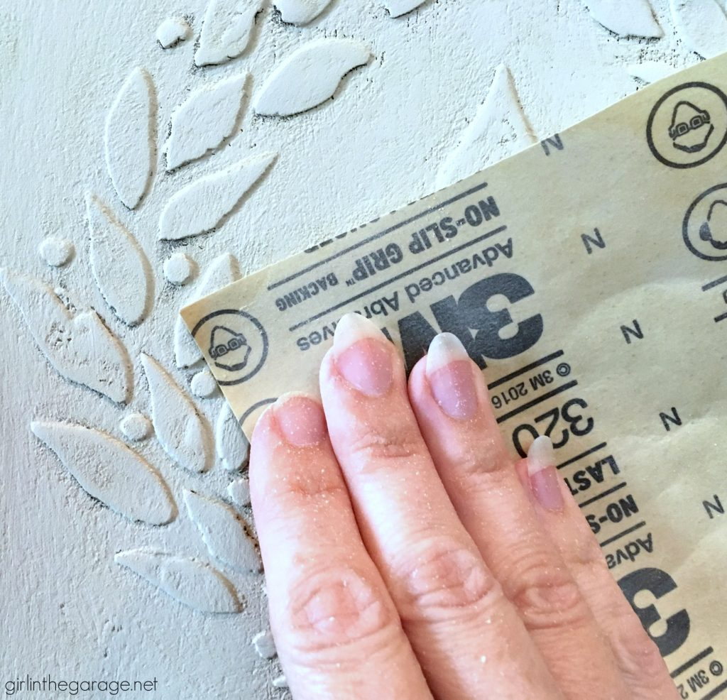 Add amazing custom texture with a raised stencil furniture makeover using spackling from the hardware store. Step by step DIY tutorial for custom embossed furniture by Girl in the Garage.