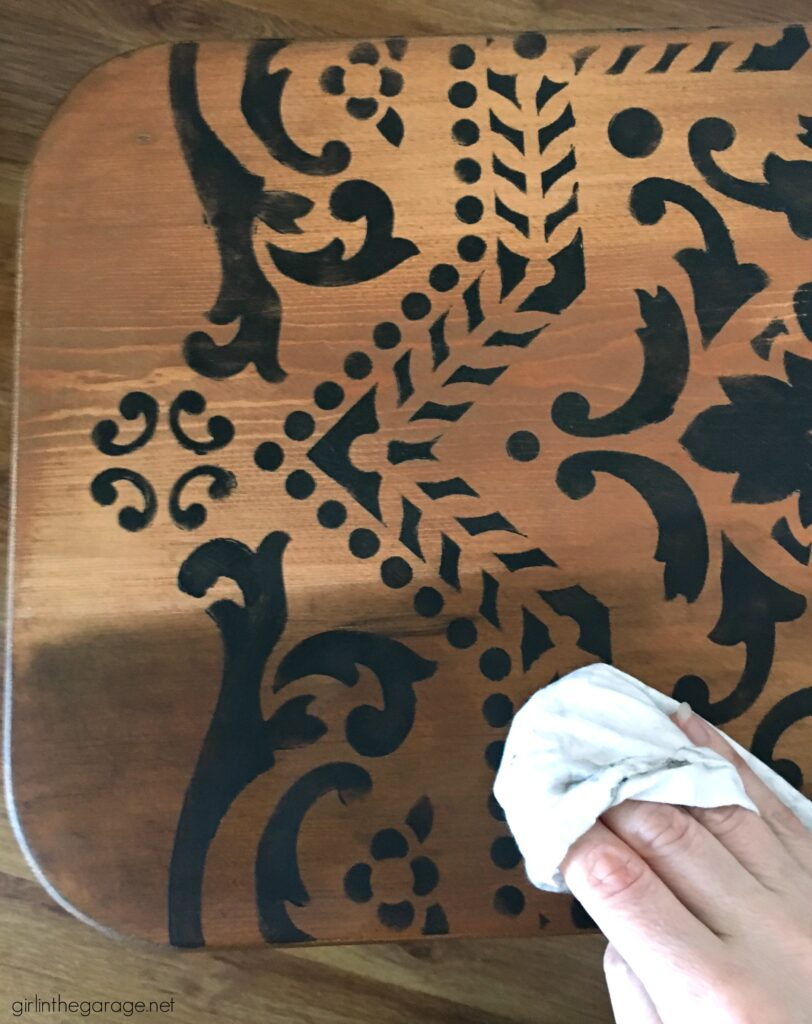 Love the black wood stain look? Learn how to stencil a table and easily stain wood black with furniture wax. By Girl in the Garage