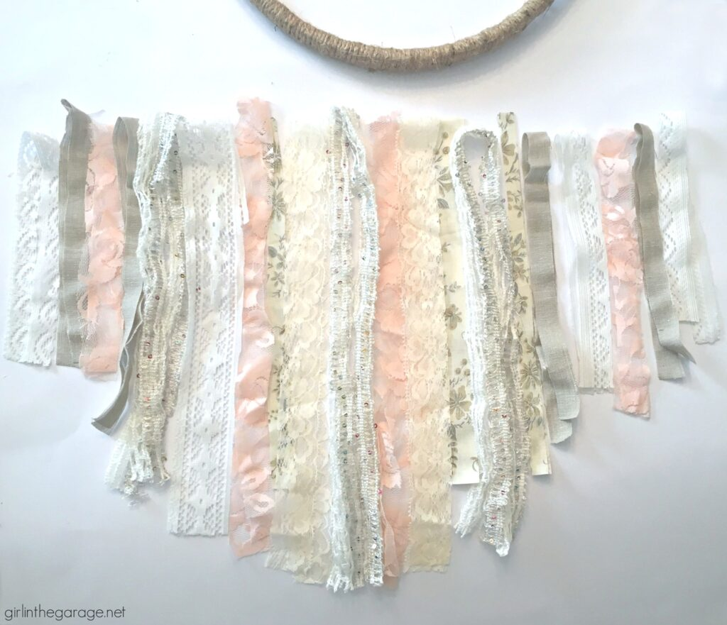 Make a stunning DIY embroidery hoop wreath with lace, ribbon, and fabric scraps. Add some flowers for fun! DIY decor ideas by Girl in the Garage