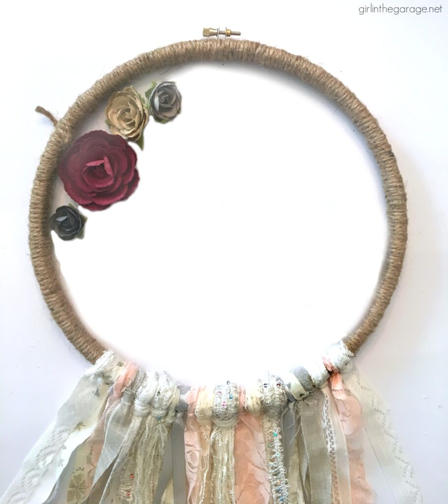 Make a stunning DIY embroidery hoop wreath with fabric scraps. Add some flowers for fun! DIY decor ideas by Girl in the Garage