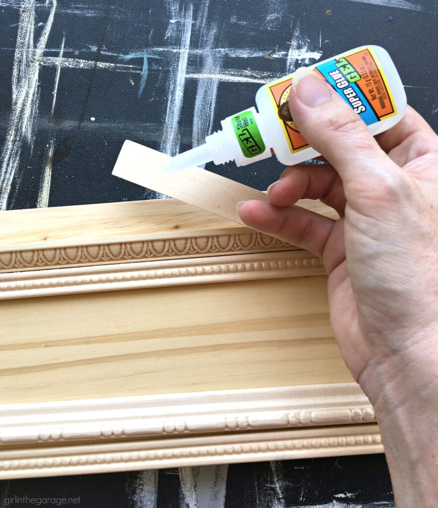 How to make a hanging coat rack with decorative trim and properly prepare, stain, and protect it with Minwax products. DIY makeover ideas by Girl in the Garage. #ad