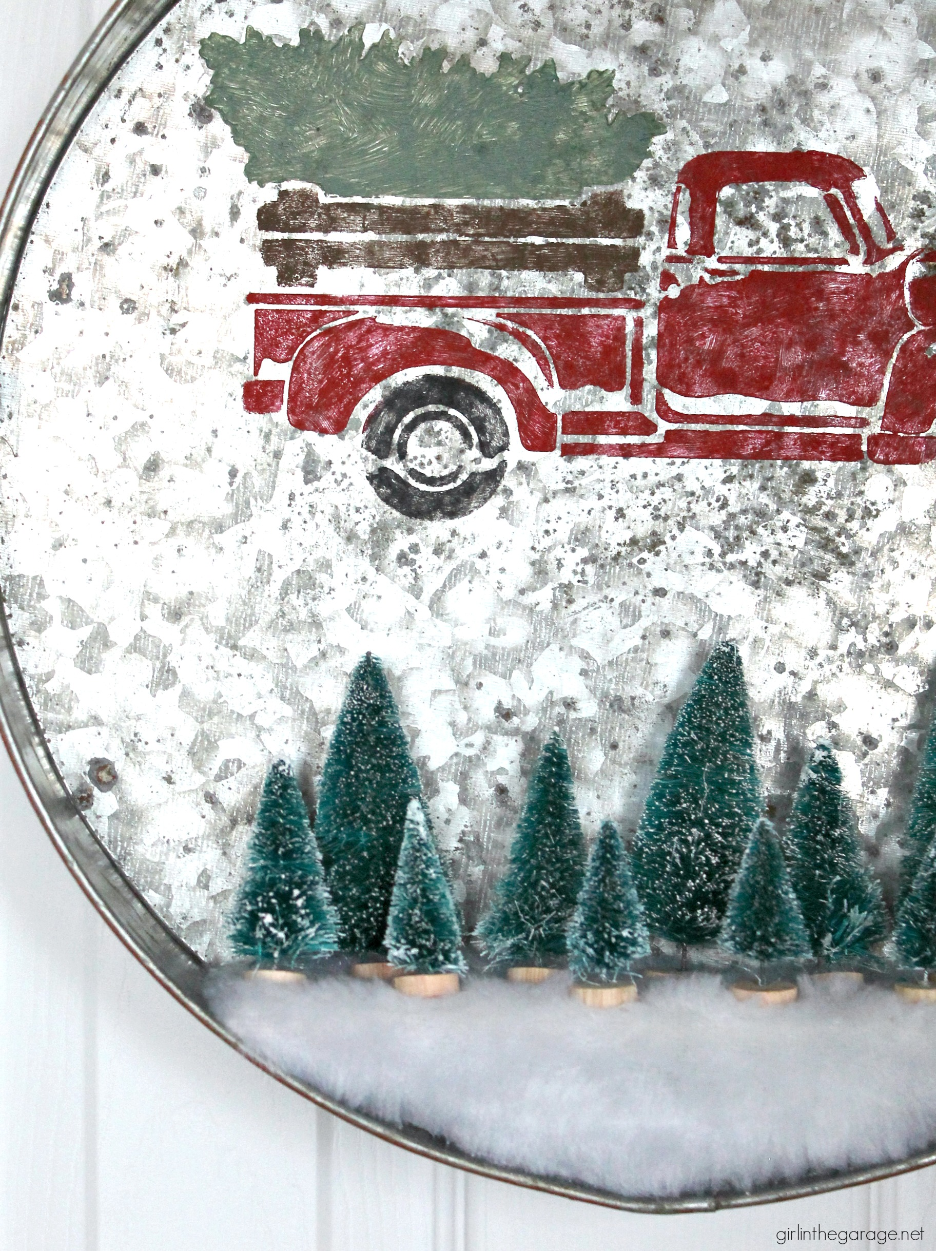 Make a DIY Christmas wreath from a repurposed metal tray - an adorable Christmas decor idea with stenciled truck and miniature bottle brush trees! By Girl in the Garage